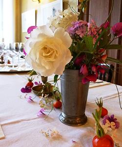 Strauß mit Rosen und Hagebutten in alter Zinnvase auf dem Tisch